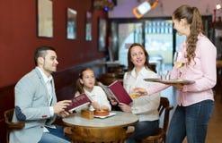 Waitress and happy family Royalty Free Stock Photo