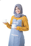 Waitress with head scarf serving coffee Stock Photography