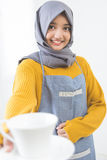 Waitress with head scarf serving coffee Royalty Free Stock Photos