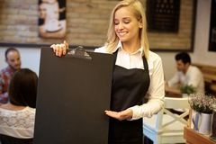 Waitress holding blackboard Royalty Free Stock Photo