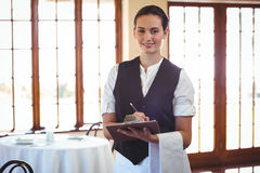 Waitress holding a clipboard. In a restaurant Stock Images