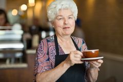 Waitress Holding Coffee Cup And Saucer In Cafe Stock Photo