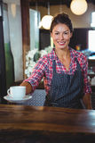 Waitress holding a cup of coffee Stock Images