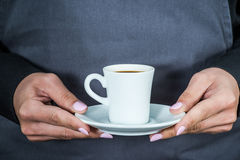 Waitress holding cup of coffee Stock Photo