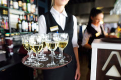 Waitress holding a dish of champagne and wine glasses at festive event Stock Photos