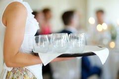 Waitress holding a dish of glasses Royalty Free Stock Image