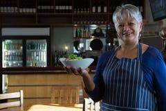 Waitress holding food bowl stock photo