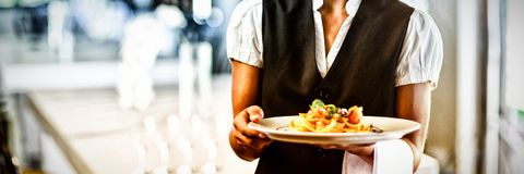 Waitress holding plate of meal in a restaurant. Portrait of smiling waitress holding plate of meal in a restaurant stock photo