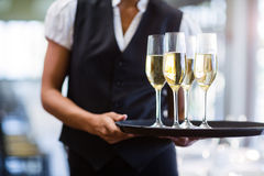Waitress holding serving tray with champagne flutes  Royalty Free Stock Images