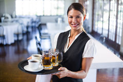 Waitress holding serving tray with coffee cup and pint of beer. Portrait of waitress holding serving tray with coffee cup and pint of beer in restaurant stock image