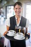 Waitress holding serving tray with coffee cup and pint of beer Stock Image