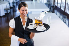Waitress holding serving tray with coffee cup and pint of beer. Smiling waitress holding serving tray with coffee cup and pint of beer in restaurant royalty free stock images