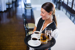 Waitress holding serving tray with coffee cup and pint of beer. Smiling waitress holding serving tray with coffee cup and pint of beer in restaurant stock photos