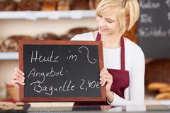 Waitress Holding Slate With Offer Written On It At Bakery. Young waitress holding slate with offer written on it at bakery counter Stock Photos