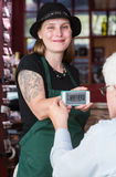 Waitress holding smart phone with coupon code. Smiling waitress in green apron holding smart phone with coupon code for customer Royalty Free Stock Image