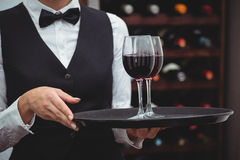 Waitress holding a tray with glasses of red wine Stock Images