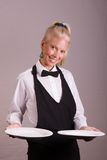 Waitress holding two plates. Assertive posed uniformed female waitress holding two white plates Royalty Free Stock Photography