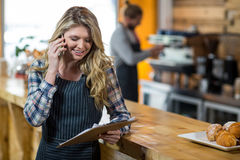 Waitress looking at clipboard while talking on mobile phone in café Stock Photography