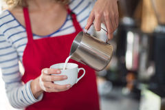 Waitress making cup of coffee at counter in cafe Stock Image