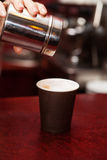 Waitress making in Takeaway cup Coffee. With foam and Cinnamon on red table Royalty Free Stock Photo