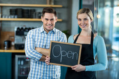 Waitress and man standing with open sign on slate in cafe. Portrait of waitress and men standing with open sign on slate in cafe Stock Photography