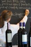 Waitress, menu board, and wine