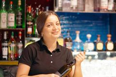 The waitress opens a bottle of white wine. A bartender woman smiles and opens a bottle of white wine for the client of the hotel bar. Shelves with bottles of Royalty Free Stock Images