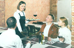Waitress placing order in front of guests Stock Image