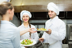 Waitress with plates at kitchen Royalty Free Stock Photography
