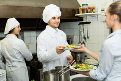 Waitress with plates at kitchen. Male cook gives to charming waitress plates with prepared meal royalty free stock image
