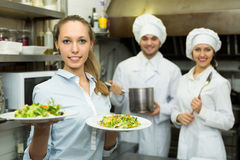 Waitress with plates at kitchen Royalty Free Stock Images