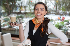 Waitress posing with cup of coffee in caf� or restaurant Royalty Free Stock Image
