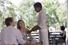 Waitress pouring white wine for couple sitting at table on restaurant balcony Royalty Free Stock Photos