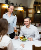 Waitress with prepared meal at table Stock Image
