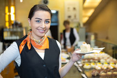 Waitress presenting cake in cafe or confectionery Royalty Free Stock Images