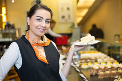 Waitress presenting cake in cafe or confectionery Royalty Free Stock Image