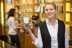 Waitress presenting cup of coffee or tea Stock Photos