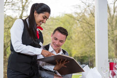 Waitress presenting the menu to a guest in restaurant Stock Photos