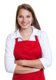 Waitress with red apron and crossed arms. On an isolated white background Royalty Free Stock Image