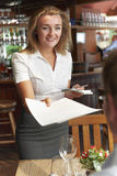 Waitress In Restaurant Handing Customer Menu Royalty Free Stock Photo