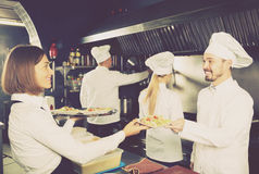 Waitress in restaurant kitchen Royalty Free Stock Images
