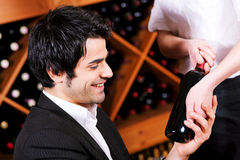 Waitress in restaurant offering red wine Royalty Free Stock Photos