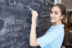 Waitress In Restaurant Writing Menu On Blackboard Stock Photography