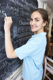 Waitress In Restaurant Writing Menu On Blackboard Stock Image