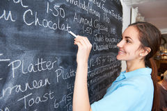 Waitress In Restaurant Writing Menu On Blackboard. Waitress In Restaurant Writes Menu On Blackboard Stock Photo