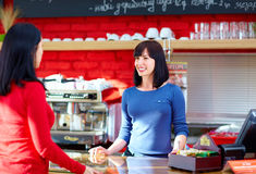 Waitress serves customer in coffee shop Royalty Free Stock Photos