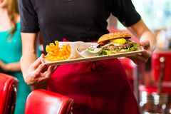 Waitress serving in American diner or restaurant. Friends or couple eating fast food with burger and fries in American fast food diner Royalty Free Stock Images