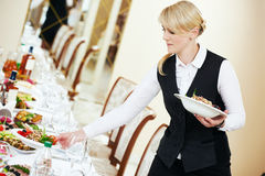 Waitress serving banquet table Stock Image