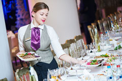 Waitress serving banquet table Stock Photo