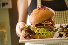 Waitress serving big hamburger Stock Photo